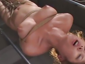 Asian bondage scene with rope suspension and forced orgasm