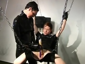 Naughty domina in latex punishing and whipping a horny slave girl