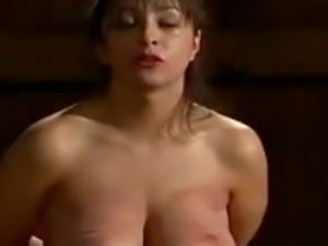 Sub hung by her tits, caned, and tortured on a triangle horse.