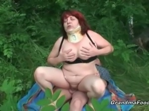 Redhead mature rides a hard cock in the woods
