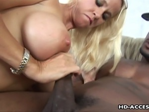 Seductive blonde MILF with a pair of large round tits slurps a big black...