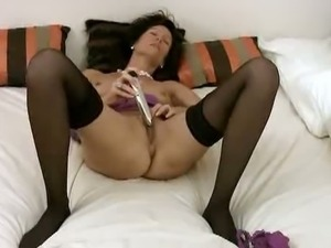 Mature woman masturbates with a toy
