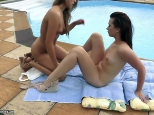 Two brunette lesbians with shaved pussies are near a swimming pool. They have...