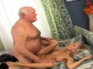 Grandpa sits on the bed, holding himself up with his...