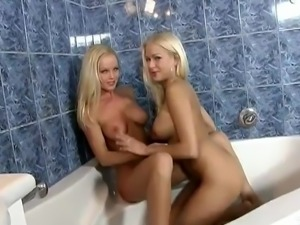 Two long-haired lesbians touching each other's pussies in the bathroom