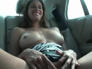 Busty brunette babe plasys with herself in a moving car