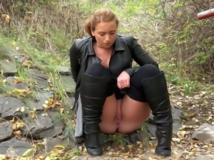Redhead amateur babe walking in the wood crouches to pee