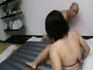 Wet chick in a purple bathing suite grabs his pecker and je
