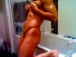 Fitness diva rubbing her sexy body with oil in the bathroom