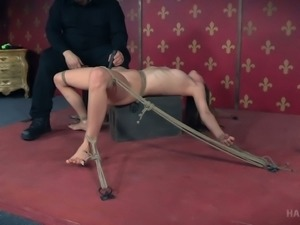 Lean white young babe stretched with ropes on the box