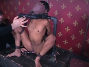 Masked dark skin bimbo chained to the steel pipes nude