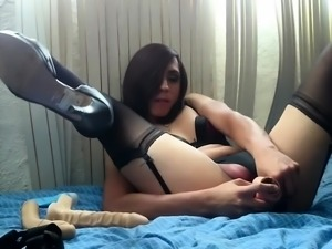 Provoking crossdresser in lingerie has fun with big toys