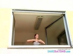 Short haired girl washes windows topless