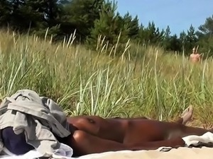 Nudist beach voyeur films a sexy ebony babe enjoying the sun